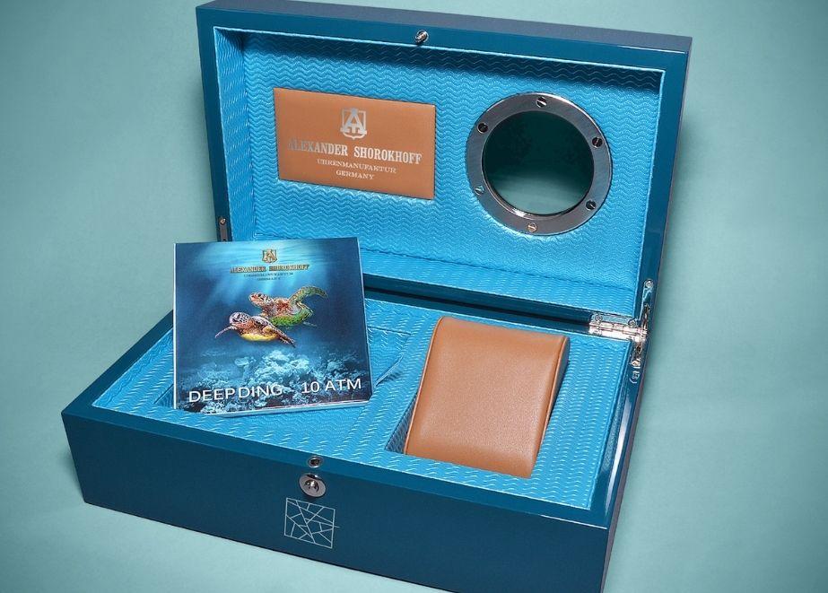 Uhrenbox in Marineblau und mit Stoffüberzug und Guckloch sowie Echtheitszertifikat auf der linken Seite der Box.